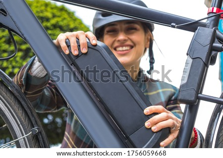 young woman holding an electric bike battery mounted on frame Royalty-Free Stock Photo #1756059668