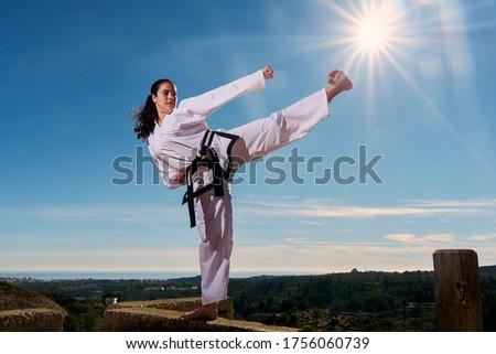 Young black belt girl kicks towards the sun like a star in the blue sky. Taekwondo martial arts. Royalty-Free Stock Photo #1756060739