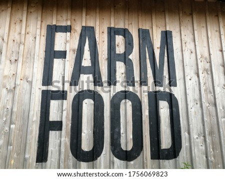 "The words ""farm food"" written on a wooden wall."