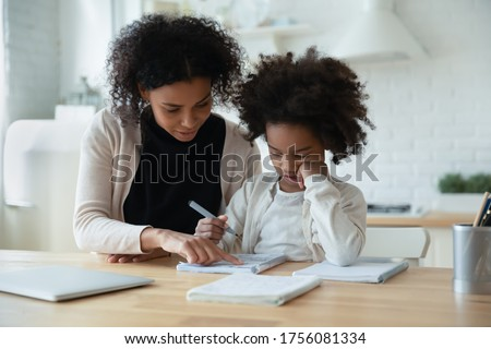 African mother helps with task little schoolgirl daughter do together schoolwork, parent explain subject, focused child listen to mum sit at table at home in kitchen. Education, homeschooling concept Royalty-Free Stock Photo #1756081334
