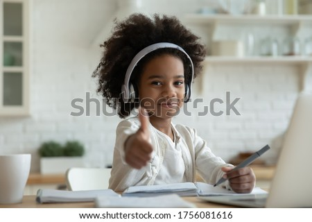 African girl in headphones enjoy e-learn sit at table showing thumbs up recommend e-study easy and interesting app for children, using modern tech. Homeschooling, clever kid and self-education concept #1756081616