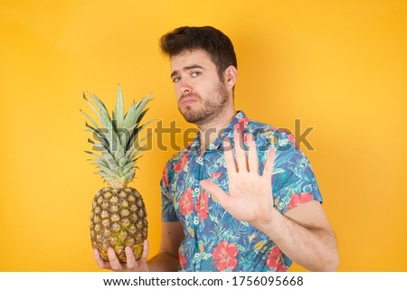 Handsome young man over isolated background afraid, terrified and disgusted expression stop gesture with both hands saying: Stay there. Panic concept.