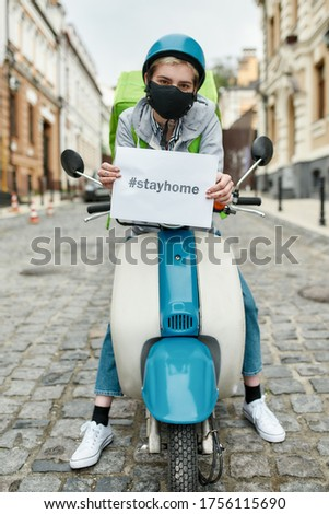 Young delivery woman in mask with thermo backpack holding a card with the inscription Stay Home, delivering food on a motor scooter. Courier, delivery service, lockdown concept. Focus on card