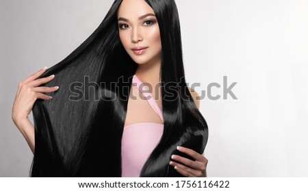 Beautiful asian model girl with shiny black and straight long hair . Keratin straightening . Treatment, care and spa procedures for hair . Chinese girl with smooth hairstyle Royalty-Free Stock Photo #1756116422