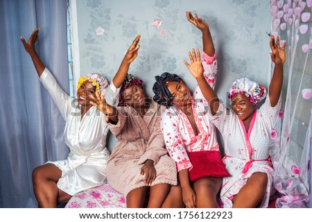 Four beautiful African women wearing robes and satin bonnet caps, laughing and having fun with hands raised up - Black millennial bridesmaids sitting, laughing - people enjoying on vacation travel  Royalty-Free Stock Photo #1756122923