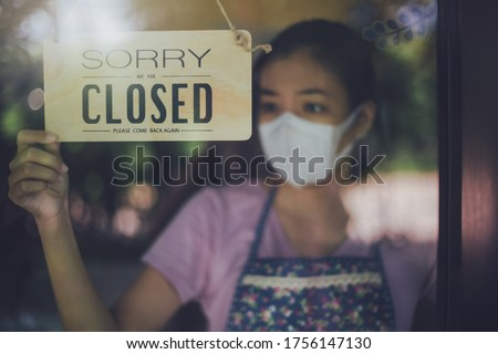 Close up shot of woman wearing mask and hand turning closed sign board on glass door in coffee shop and restaurant after coronavirus lockdown quarantine.Business crisis concept.