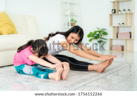 Asian Mother and daughter doing fitness exercises in living room at home to maintain physical and mental health and wellbeing get exercise into your daily routine while social distancing. #1756152266