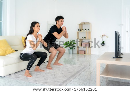 Young Asian couple doing squats training together and looking TV at home, man and woman working out together standing in living room, fit pair performing fitness exercise with partner. #1756152281