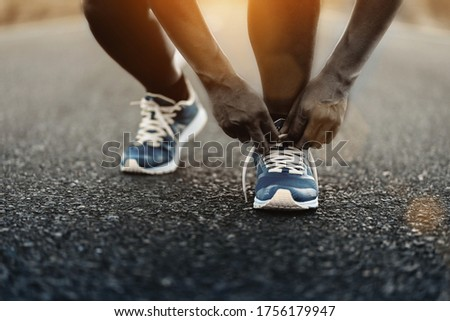 Young fitness African American man is running and jogging an outdoor workout with tying shoelaces on road for lifestyle health.