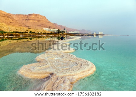 Skies merge with sea on horizon. Evaporated salt protrudes above water. Dim winter day over the Dead Sea. The concept of active and photo tourism. Israel
