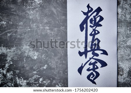 """Calligraphy - Kyokushinkai karate symbol on wooden background.  """"Kyokushin"""" is a style of stand-up, full contact karate and is Japanese for """"the ultimate truth"""". Top view. Copy space.  Royalty-Free Stock Photo #1756202420"""