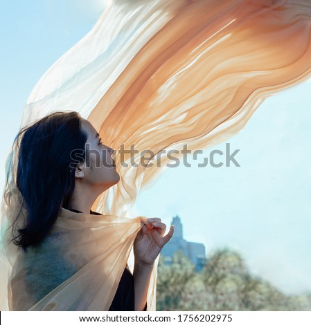 Asian girl with a flying orange scarf against a blue sky