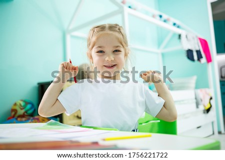 Adorable toddler girl drawing with pencils at home sitting at the table. Creative child sitting in a room learning to draw. Toddler girl doing homework at home. #1756221722
