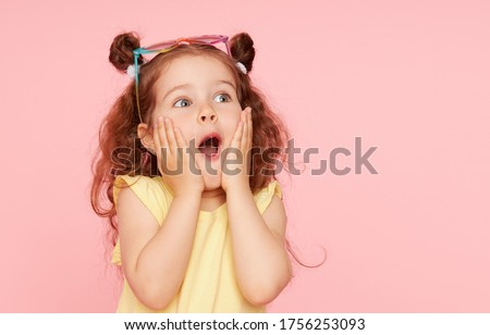 Portrait of surprised cute little toddler girl  in sunglasses over pink background.  Child model have fun and jump. Advertising childrens products #1756253093
