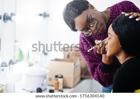 African American woman applying make-up by make-up artist at beauty saloon. Royalty-Free Stock Photo #1756304540