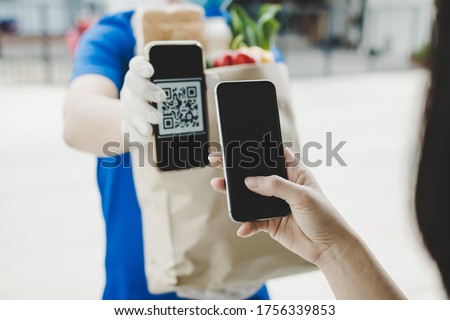 woman customer using digital mobile phone scan QR code paying for buying fresh food set bag from food delivery service man, express delivery, digital payment technology and fast food delivery concept #1756339853
