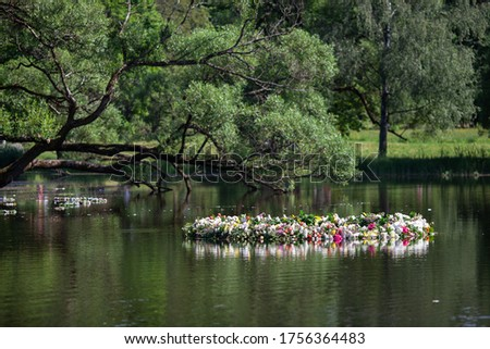 Beautiful  huge wreath of fresh flowers on the water. The celebration of Ivan Kupala (St. John Day). Old holiday dedicated to the summer solstice. Selective focus. #1756364483