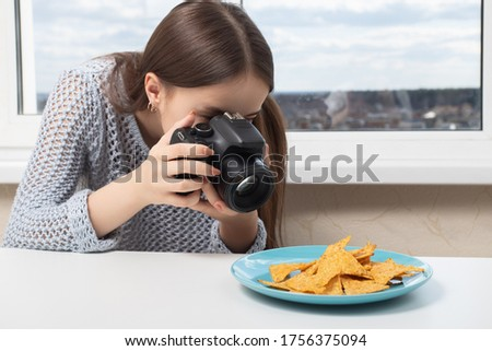 Photoshop for beginners. Learn to take pictures correctly. Girl photographer takes nachos chips on a plate
