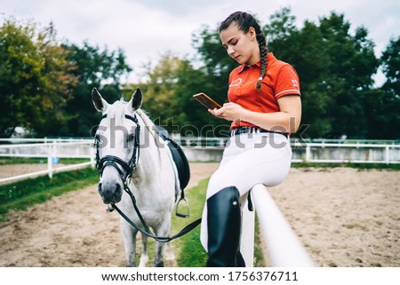 Side view of female horse rider sitting on metal fence and holding bridle in hand while looking at smartphone near horse #1756376711