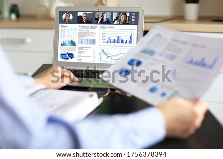 Business woman in headphones talking to her colleagues in video conference. Multiethnic business team working from home using laptop, discussing financial report of their company. Royalty-Free Stock Photo #1756378394