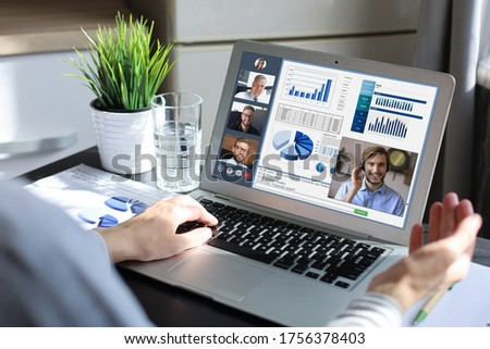 Business woman in headphones talking to her colleagues in video conference. Multiethnic business team working from home using laptop, discussing financial report of their company. Royalty-Free Stock Photo #1756378403
