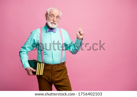 Photo of funny aged grandpa teacher hold books lecturer university college direct finger empty space black board wear specs shirt suspenders bow tie pants isolated pink pastel color background