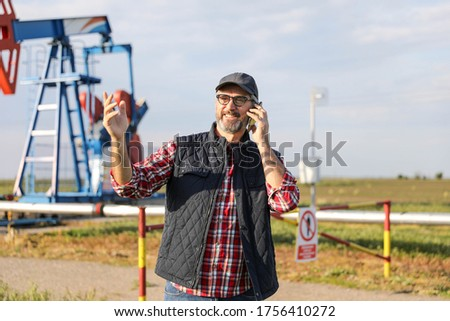 Portrait of man engineer in the oil field wearing red helmet and work clothes holding wrenches in his hand and radio in jacket pocket. Blurry pump jack and wellhead background. Oil and gas concept. #1756410272
