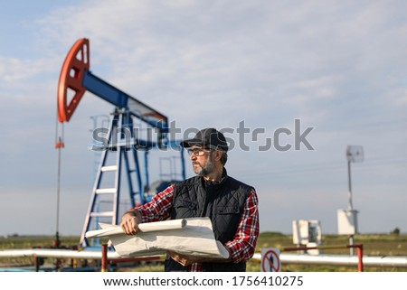 Portrait of man engineer in the oil field wearing red helmet and work clothes holding wrenches in his hand and radio in jacket pocket. Blurry pump jack and wellhead background. Oil and gas concept. #1756410275