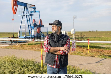 Portrait of man engineer in the oil field wearing red helmet and work clothes holding wrenches in his hand and radio in jacket pocket. Blurry pump jack and wellhead background. Oil and gas concept. #1756410278