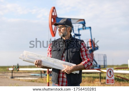 Portrait of man engineer in the oil field wearing red helmet and work clothes holding wrenches in his hand and radio in jacket pocket. Blurry pump jack and wellhead background. Oil and gas concept. #1756410281