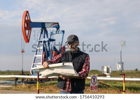Portrait of man engineer in the oil field wearing red helmet and work clothes holding wrenches in his hand and radio in jacket pocket. Blurry pump jack and wellhead background. Oil and gas concept. #1756410293
