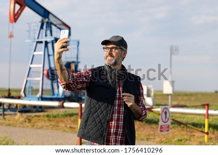 Portrait of man engineer in the oil field wearing red helmet and work clothes holding wrenches in his hand and radio in jacket pocket. Blurry pump jack and wellhead background. Oil and gas concept. #1756410296