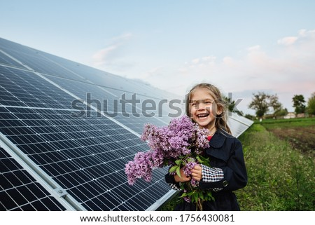 A child with a future of alternative energy and sustainable energy. The child holds flowers on a background of solar panels, photovoltaic. Environmental friendliness and clean energy concept. #1756430081