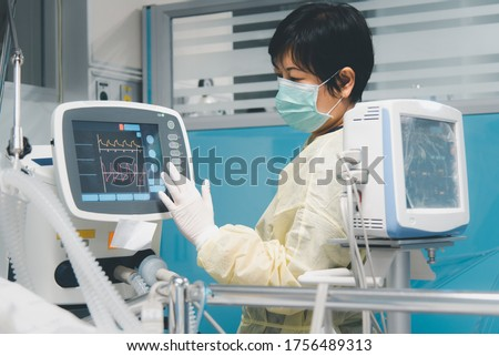 Doctor use monitor with vital signs for medical care of the flu covid19, corona virus, CRE. or VRE. infected elder patient 80s years old on patient bed in intensive care unit (ICU.) room at hospital Royalty-Free Stock Photo #1756489313