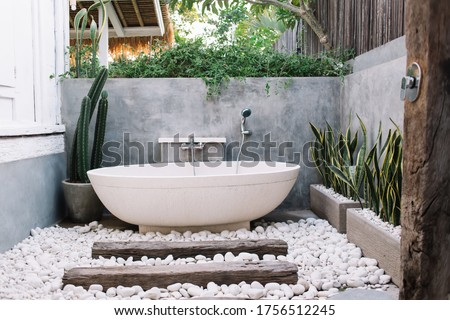 Modern outdoor bathroom with oval white ceramic bathtub decorated with green exotic plants and pebbles on terrace of luxury villa in Bali #1756512245