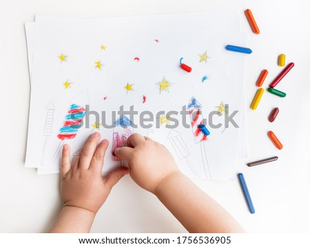 Toddler sits on windowsill and draws colorful fireworks. Child's picture to 4th of July celebration. Independence Day of USA symbol.