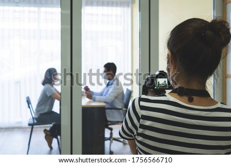 young asian woman using camera to take a photo of doctor and patient scene in studio. photogarpher and stocker job concept