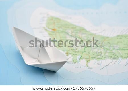 Paper boat navigating a flat map