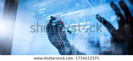 Project manager working and update tasks with milestones progress planning and Gantt chart scheduling virtual diagram.Businessman hand pressing an imaginary button on virtual screen