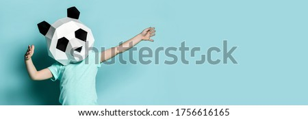 Baby boy kid in polygonal panda mask dancing with hands spread up popular sign on pastel color blue mint background. Banner with text copy space Royalty-Free Stock Photo #1756616165