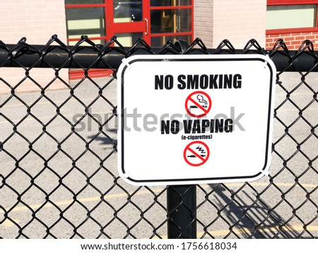 Close up of a no smoking, no vaping sign fixed on chain fence in front of school playground area.