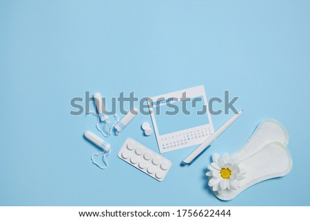 menstrual sanitary tampon, pad, pain pills during menstruation and white chamomile flower on blue background, feminine calendar with mock up. Feminine hygiene products. top view. Royalty-Free Stock Photo #1756622444