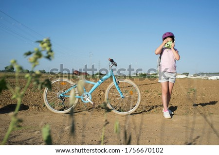 Cute little girl shooting at countryside with her instant picture photo camera. She is got a nice retro bike parked on side