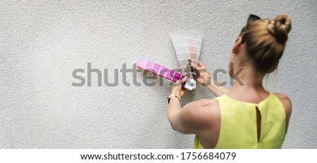 woman choosing paint color from swatch for house stucco exterior facade. copy space Royalty-Free Stock Photo #1756684079