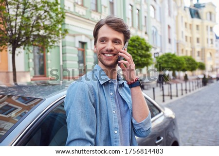 Delighted young male glancing aside while having phone conversation near car Royalty-Free Stock Photo #1756814483