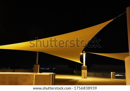 Sun sail shades on the rooftop of a parking structure.