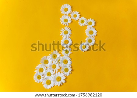 A musical note made of white daisy flowers on a yellow background. Musical composition, songwriting, creative performance. The concept of gentle music.