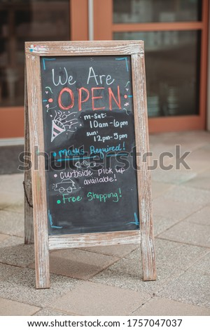 Reopening of a small business activity after the covid-19 emergency, ended the lockdown and quarantine. A business sign that says now we are open support local businesses hang on door at entrance.