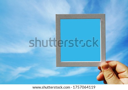 Hand holding a wooden frame on blue sunrise sky background. Care, safety, memory or painting concept.