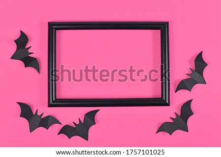 Halloween flat lay with black flying paper craft bats around empty picture frame on bright pink background